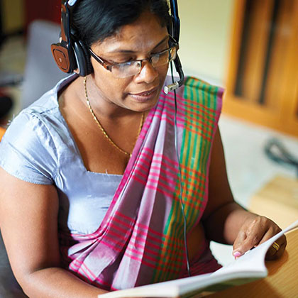 Person Wearing Headphones and Reading a Book