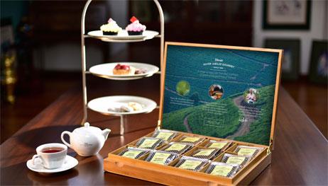 Various Tea Sachets With a Tea Cup, Teapot and Various Desserts
