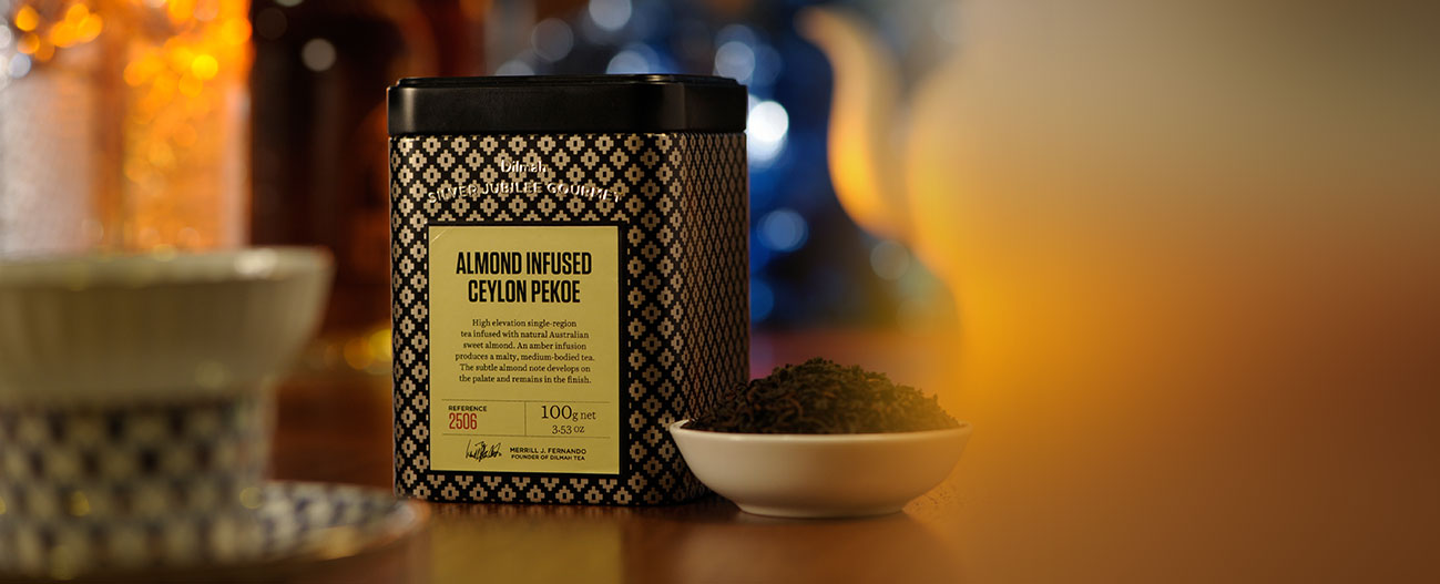 Container of Almond Infused Ceylon Pekoe Tea and Dried Tea Leaves