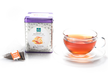 Container of Ceylon Breakfast Tea and a Tea Bag next to a Cup of Tea