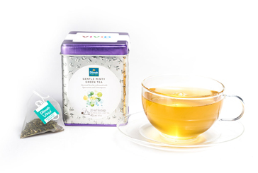 Container of Gentle Minty Green Tea and a Tea Bag next to a Cup of Tea